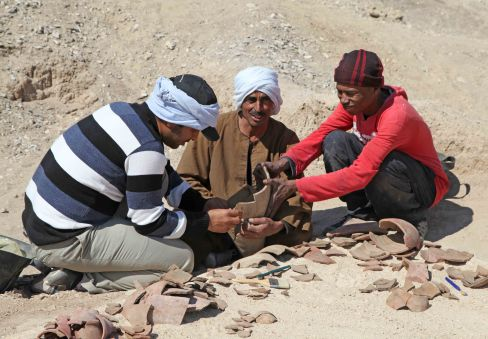 Inspector Mohammed Ibrahim, Azib, and Ali reconstructing pottery